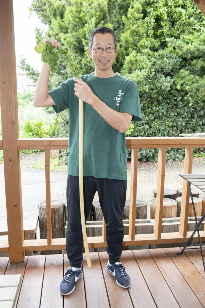 守口大根の見本を持つハタケタナカの田中稔さん